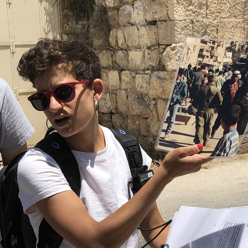 On an empty street in Hebron, Frima, my tour guide for Breaking the Silence Israel, shows us a picture of the same street filled with people 1994.