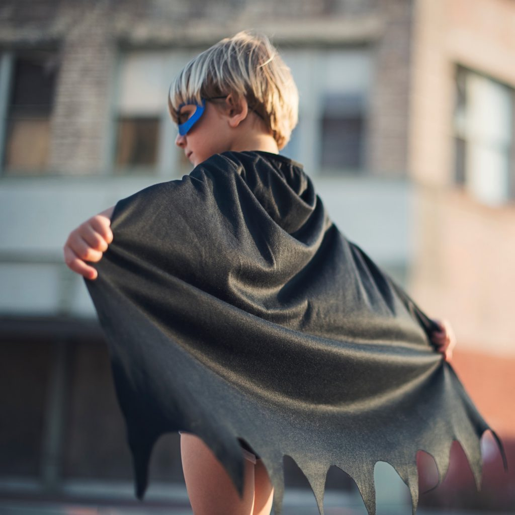 A young superhero in a cape planning to make the difference.