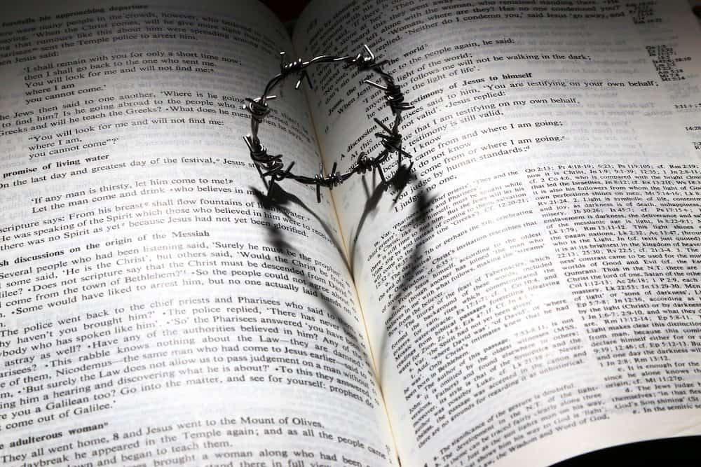 The reflection of a crown of thorns in the shape of a heart lies in the pages of the Bible as if to say, you are loved!